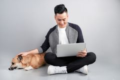 Handsome young businessman is using laptop while sitting with his dog on floor.  stock photos