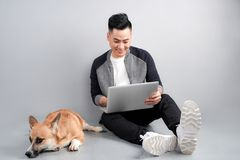 Handsome young businessman is using laptop while sitting with his dog on floor.  stock images