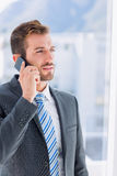 Handsome young businessman using mobile phone. Over blurred background in office Stock Image