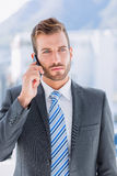 Handsome young businessman using mobile phone. Over blurred background in office Royalty Free Stock Images