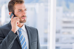 Handsome young businessman using mobile phone. Over blurred background in office Royalty Free Stock Photography