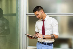 Handsome young businessman using tablet PC. Handsome young businessman in his office working and using tablet PC, looking down, serious Stock Photos