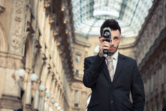 Handsome young businessman using a vintage film camera Stock Images