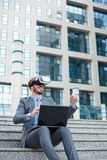 Young businessman using VR goggles and making hand gestures, working on a laptop in front of an office building stock photo