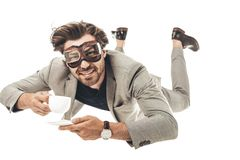 handsome young businessman in vintage aviation goggles falling with cup of coffee stock photos