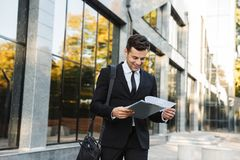 Handsome young businessman walking outdoors near business center with clipboard royalty free stock photos