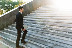 Handsome young businessman walking outdoors at the street holding clipboard royalty free stock photography