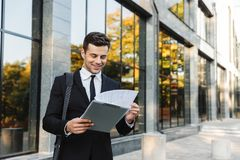 Handsome young businessman walking outdoors at the street holding clipboard royalty free stock images