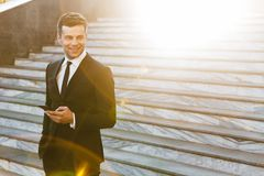 Handsome young businessman walking outdoors at the street using mobile phone stock photo