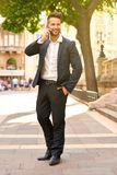 Young businessman talking on a phone on the sunny street Royalty Free Stock Images