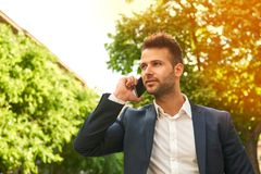 Young businessman talking on a phone on the sunny street Stock Photography