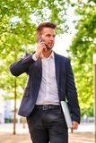 Young businessman walking on the sunny street and talking on a p Royalty Free Stock Images