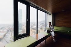 Handsome young businessman wearing bath robe on the bed with laptop in modern room. Self-employed person using laptop in. Penthouse and looking at sunny city Stock Images