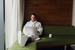 Handsome young businessman wearing bath robe on the bed with laptop in modern room. Self-employed person using laptop in. Penthouse and looking at sunny city Royalty Free Stock Images