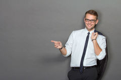 A handsome young businessman wearing glasses and smiling. Vertic. A protrait of a handsome young businessman wearing glasses and smiling pointing to copyspace Royalty Free Stock Images