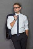 A handsome young businessman wearing glasses and smiling. Vertic. A protrait of a handsome young businessman wearing glasses and smiling. Vertical shot Stock Photo