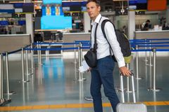 Handsome young businessman in white shirt  stretching out his ticket while standing in front of the airline check in counter in th royalty free stock image