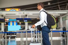 Handsome young businessman in white shirt  stretching out his ticket while standing in front of the airline check in counter in th stock photos