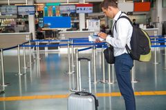 Handsome young businessman in white shirt  stretching out his ticket while standing in front of the airline check in counter in th royalty free stock photography