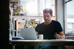 Handsome young businessman working at his desk Stock Photos