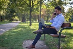 Handsome young businessman working on his laptop in the park stock images