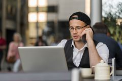 Young businessman working with laptop and phone at outdoor cafe Royalty Free Stock Photo