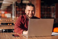 Handsome young businessman working at laptop in restaurant and looking at camera. royalty free stock photos