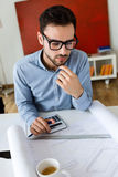 Handsome young businessman working in the office. Stock Image