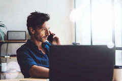 Handsome young businessman working at sunny work place on laptop.Elegant Man using smartphone while sitting at the royalty free stock photography