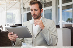 Handsome young businessman working on tablet drinking espresso Royalty Free Stock Photo