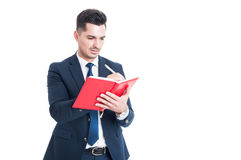 Handsome young businessman writing notes on a notebook Royalty Free Stock Photography