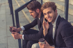 Handsome young businessmen with gadget Stock Photos