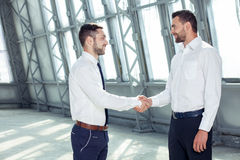 Handsome young businessmen are greeting each other Stock Photos