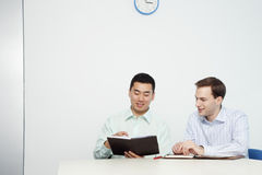 Handsome Young Businessmen Reviewing Day Planner Royalty Free Stock Image