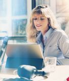 Handsome young businesswoman working at the modern office loft.Coworker using electronic touch tablet computer on sunny. Workplace.Vertical. Blurred background royalty free stock photos