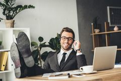 Handsome young call center worker with legs. On table Stock Photo
