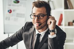 Handsome young call center worker looking. At camera Stock Photo