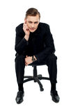 Handsome young caucasian male sitting on chair Stock Photography