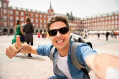 Handsome young caucasian tourist man happy and excited taking a selfie in Plaza Mayor, Madrid Spain. Attractive young caucasian tourist student man having fun Stock Photo