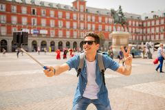 Handsome young caucasian tourist man happy and excited taking a selfie in Plaza Mayor, Madrid Spain. Attractive young caucasian tourist student man having fun Stock Photography