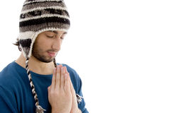 Handsome young caucasian in winter cap praying Stock Image