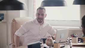 Handsome young CEO businessman talking, laughing at office meeting. Confident happy boss at his workplace slow motion. stock video