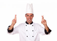 Handsome young chef crossing his fingers. Portrait of handsome 20-24 years young chef on white uniform crossing his fingers while smiling at you on isolated royalty free stock photography