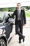 Handsome young classic car salesman standing at the dealership Stock Photo