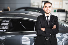 Handsome young classic car salesman standing at the dealership Royalty Free Stock Photo