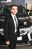 Handsome young classic car salesman standing at the dealership in front of new car Stock Image