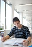 Handsome young college student in a library Royalty Free Stock Photo