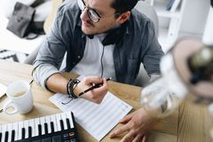 Composer. Handsome young composer writing notes at workplace stock photo
