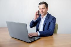 Handsome young concentrated attractive man using cellphone while working with laptop in the office Stock Image