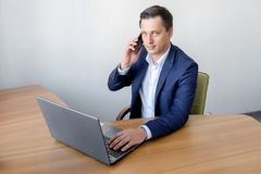 Handsome young concentrated attractive man using cellphone while working with laptop in the office Royalty Free Stock Image